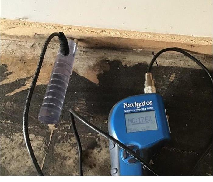 a blue small equipment with a prong stuck in the drywall