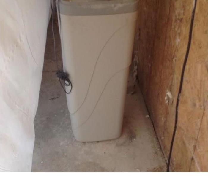 water filter in an empty room with wood walls exposed