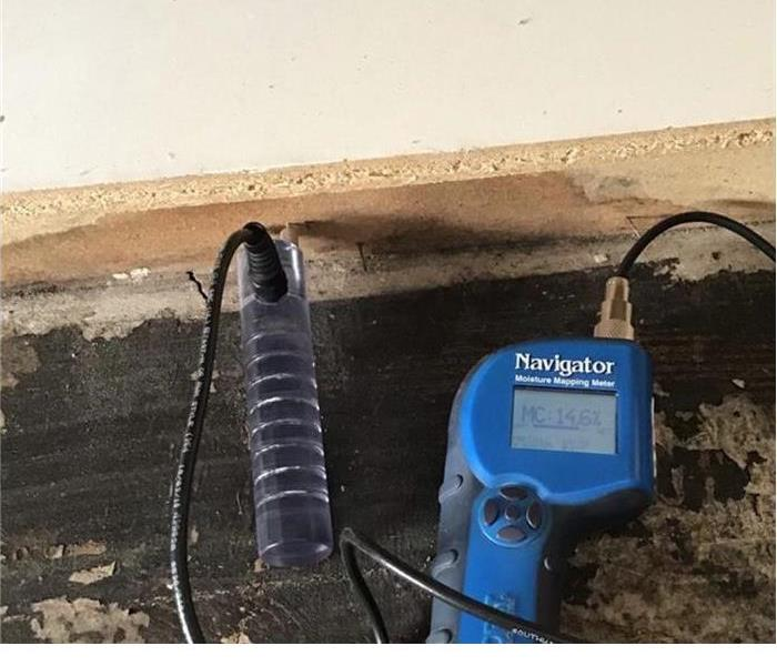 bare floor with a blue moisture meter within the wall