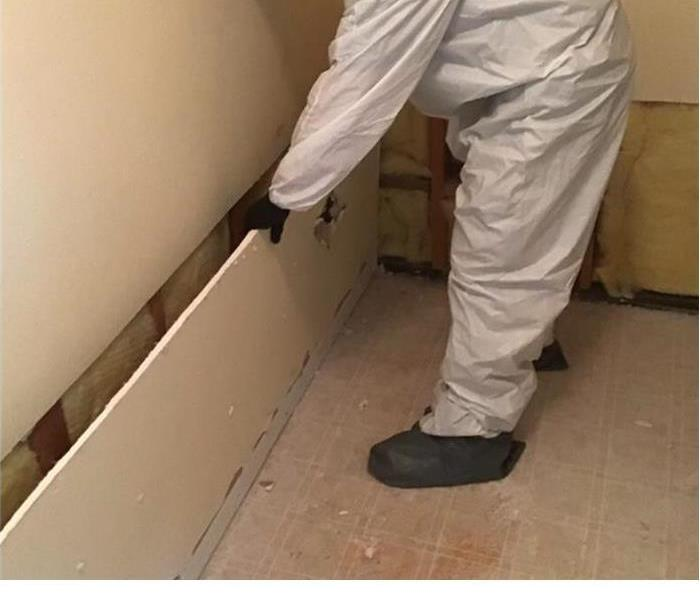 Servpro technician with a suit on removing a piece of drywall