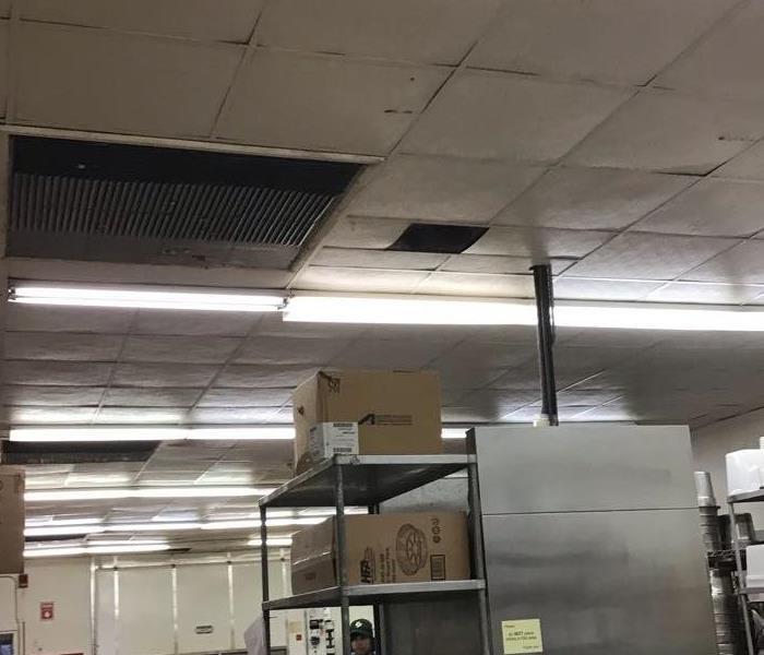 commercial kitchen with wet ceiling tiles with kitchen equipment around the floor